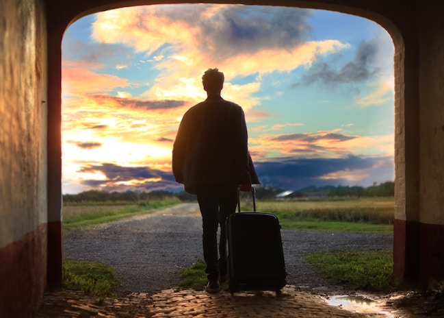 Silhouette of man with suitcase looking out to sunrise